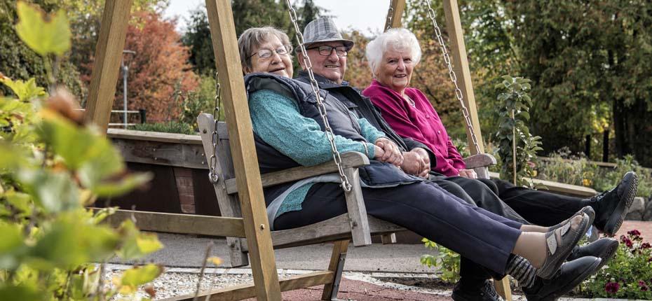 Dieses Bild zeigt drei fröhliche Senior*innen auf einer Schaukel